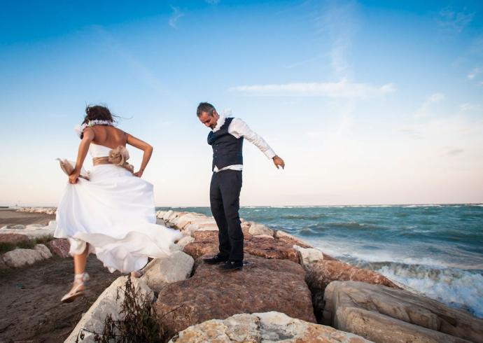 Il fotografo ritrae la coppia di sposi mentre saltano di gioia in riva al mare