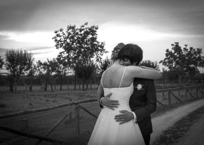 Abbraccio degli sposi alla luce del tramonto