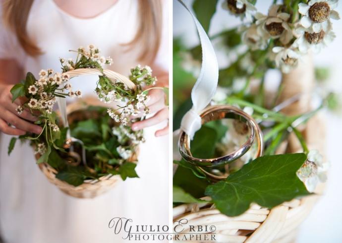 Fedi nuziali dentro un cestino di vimini riempito di fiori